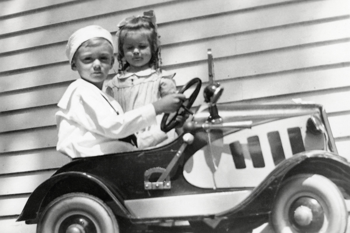 Ralph Warren Stanley Driving his 1933 Steelcraft Chevrolet Pedal Car with Ruth Celestia Stanley