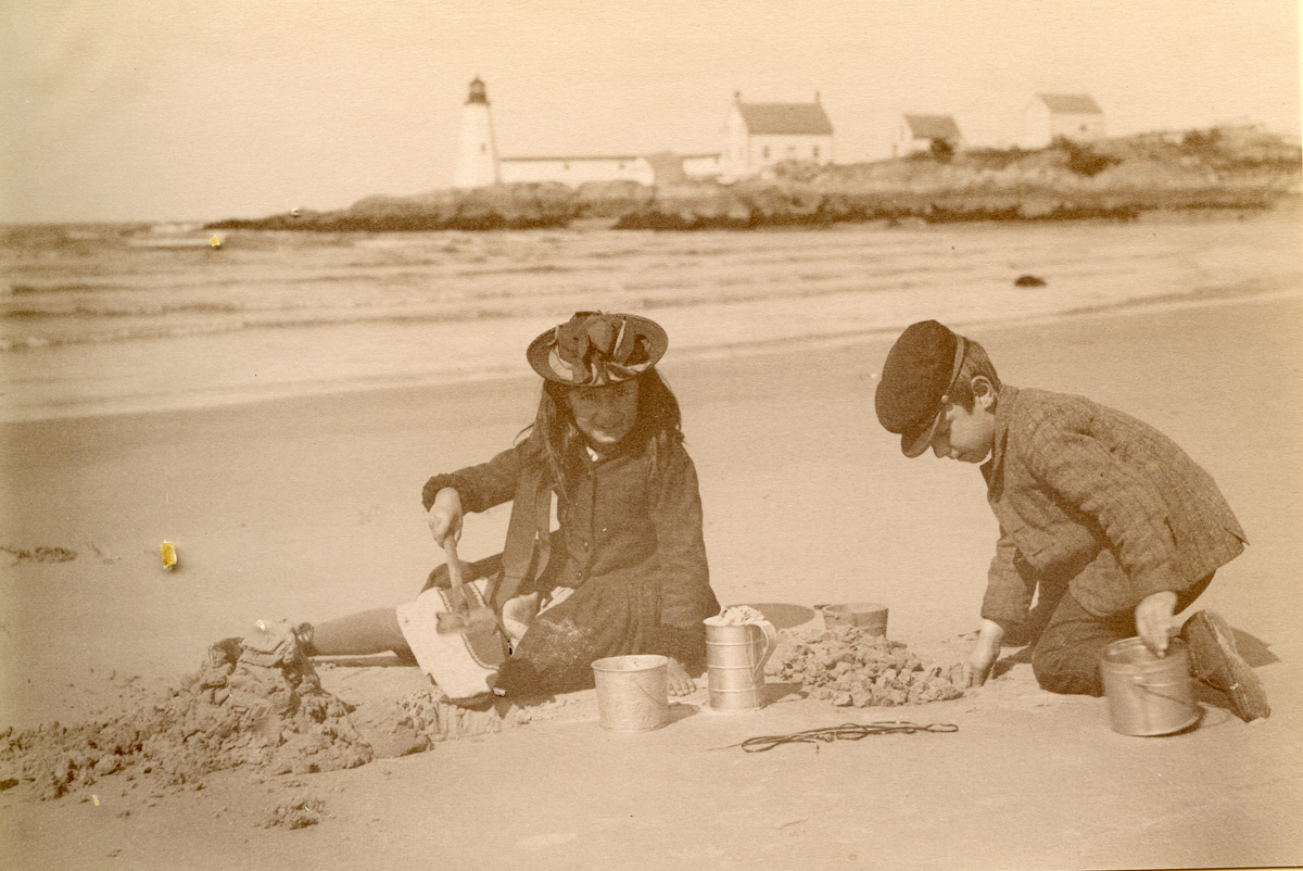 Children Digging in the Sand Near Lighthouse