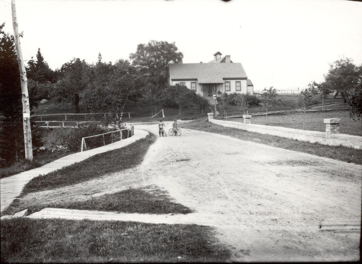 The Nathan Clark House with Boy and Girl on Bicycles by the Deacon's Cove Headwall